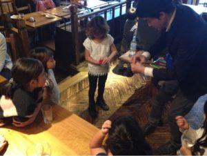 子供と一緒にシルクのハンカチを消しているところ 日本を去るご家族の送別会にマジシャンの子供向けマジックショー in ゼスト キャンティーナ 西麻布 港区