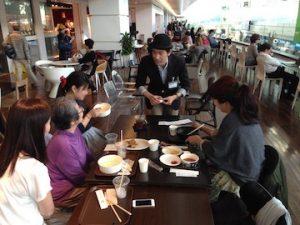 食事中の家族にマジシャンがカードマジックを披露