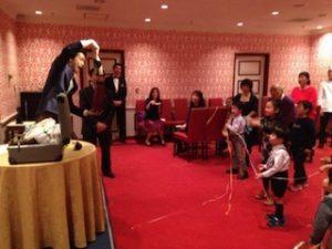ホテルの宴会場で開催されたご家族参加のクリスマスパーティーでマジシャンのマジックショー