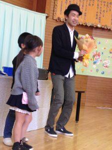 幼稚園児から花束をもらうマジシャンひろしつちや