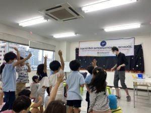 元気に手をあげる子供たち 東京ベイインターナショナルサマースクールでマジシャンの子供向けマジックショーを英語で