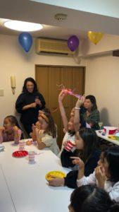投げテープを掲げる子 8歳の娘さんのお誕生会でマジシャンの出張/派遣マジックショー 東京都港区