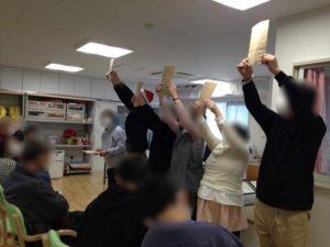 袋を高々と掲げる 就業継続支援ライブリィ工房のクリスマス&忘年会イベントでマジシャンのマジックショー 東京都東大和市