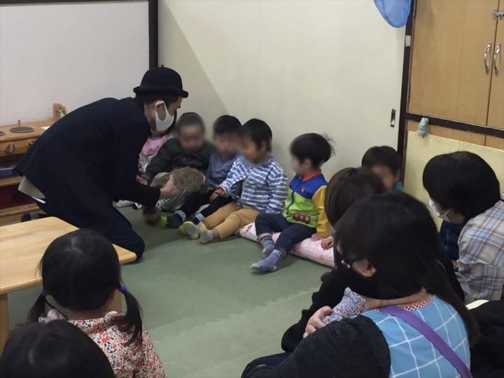 1歳児クラスでロッキーラクーンを触る園児 保育園の父母の会主催のお楽しみ会イベントでマジシャンのマジックショー 東京都練馬区