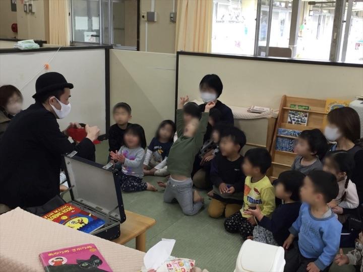 2、3歳児クラスで両手を上げる園児 保育園の父母の会主催のお楽しみ会イベントでマジシャンのマジックショー 東京都練馬区