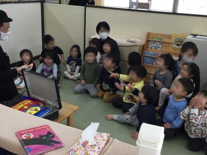 2、3歳児クラスで光に指差す子供 保育園の父母の会主催のお楽しみ会イベントでマジシャンのマジックショー 東京都練馬区