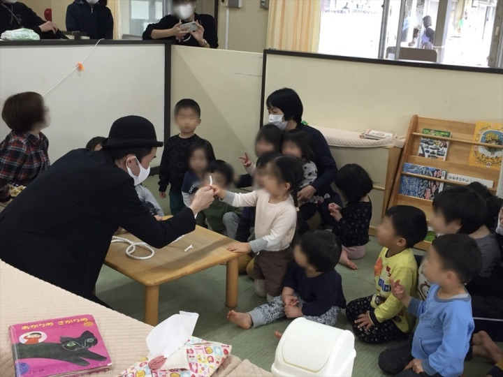 2、3歳児クラスでチョキでロープを切る園児 保育園の父母の会主催のお楽しみ会イベントでマジシャンのマジックショー 東京都練馬区