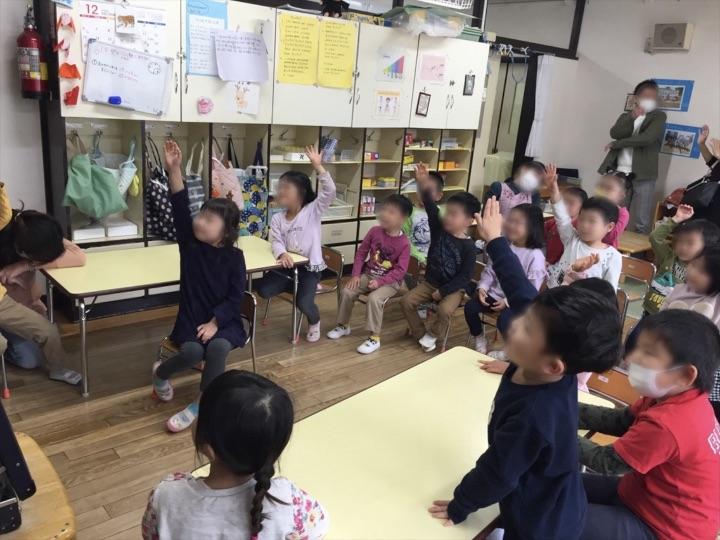 5歳児クラスで手を挙げる園児たち 保育園の父母の会主催のお楽しみ会イベントでマジシャンのマジックショー 東京都練馬区