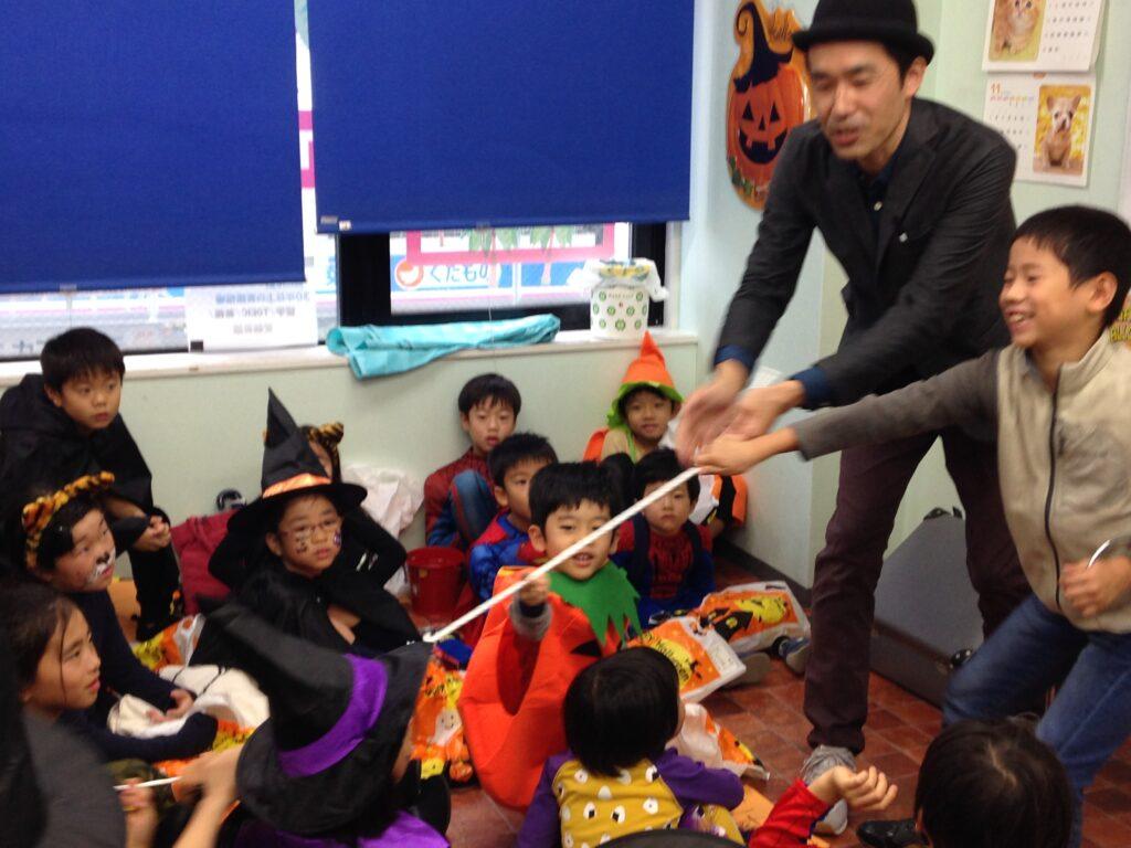 子供とロープを引っ張り合うマジシャン 英語教室のハロウィンパーティーで出張マジシャンの子供向けマジックショー in 東京都世田谷区九品仏