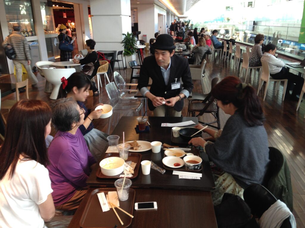 食事中の家族に出張マジシャンがカードマジックを披露 羽田空港 アッパーデッキトウキョウ6周年 記念イベント/ 出張マジシャンひろしつ